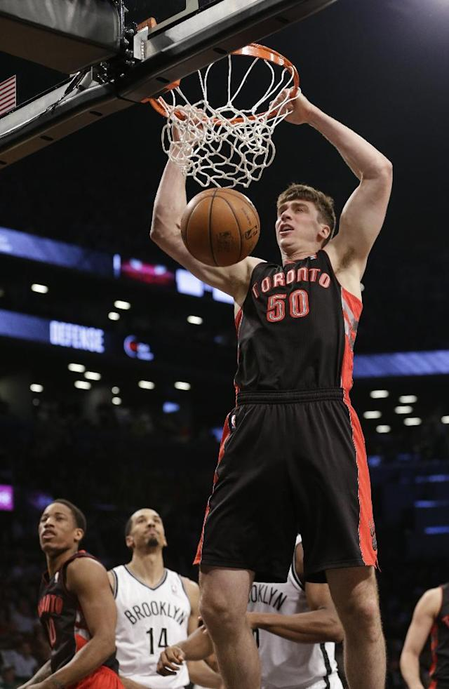 Toronto Raptors' Tyler Hansbrough (50) dunks as Brooklyn Nets' Shaun Livingston (14) watches during the first half of Game 3 of an NBA basketball first-round playoff series Friday, April 25, 2014, in New York. (AP Photo/Frank Franklin II)