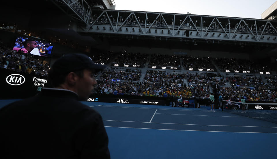 Spectators use their mobile phones to illuminate the court after the lights went out during the first round singles match between Australia's Nick Kyrgios and Italy's Lorenzo Sonego at the Australian Open tennis championship in Melbourne, Australia, Tuesday, Jan. 21, 2020. (AP Photo/Andy Wong)