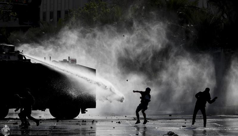 Demonstrators clash with a police water cannon during an anti-government protest in Santiago, Tuesday, Nov. 5, 2019. Chileans have been taking to the streets and clashing with the police to demand better social services and an end to economic inequality, even as the government announced that weeks of demonstrations are hurting the country's economic growth. (AP Photo/Esteban Felix)