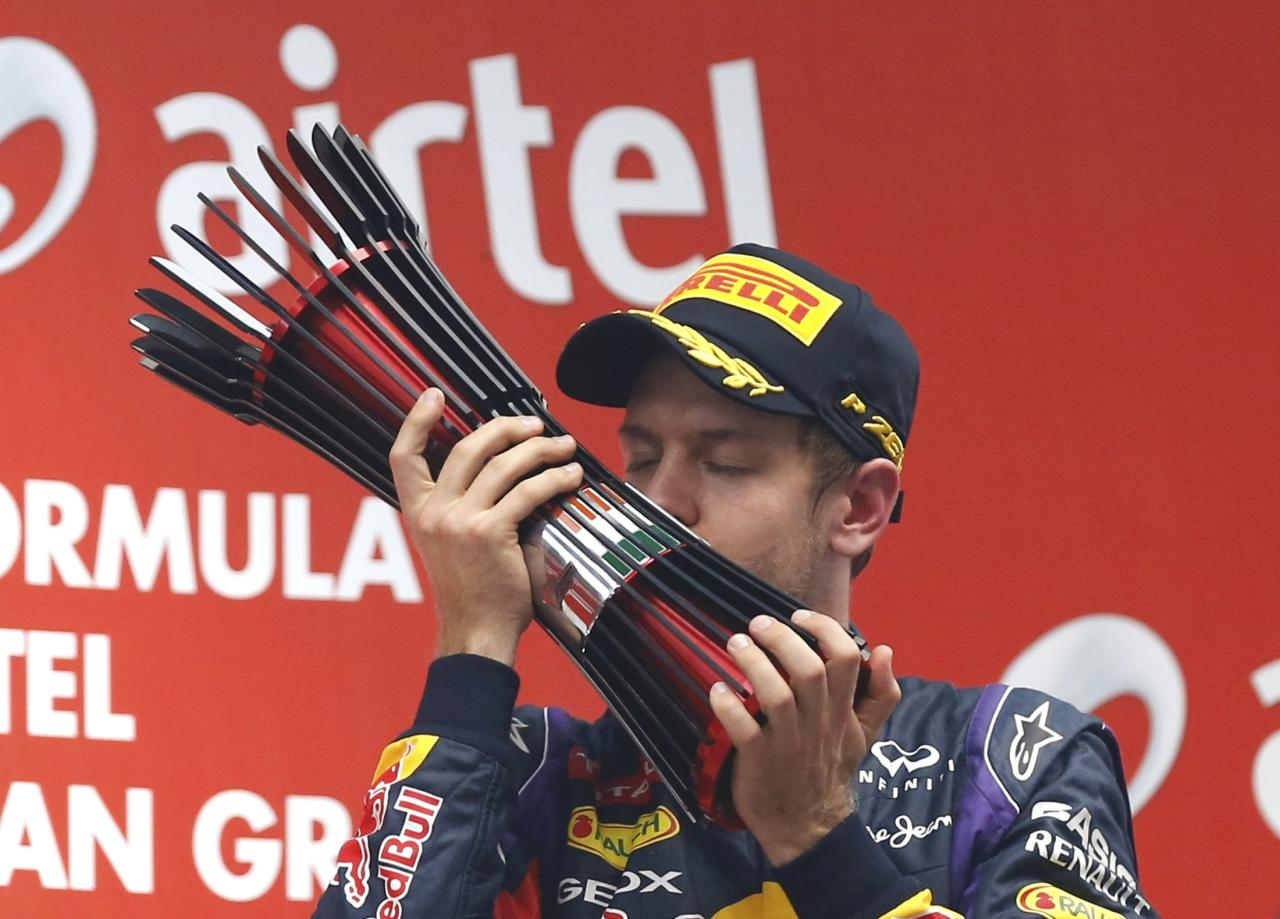 Red Bull Formula One driver Sebastian Vettel of Germany kisses his trophy on the podium after winning the Indian F1 Grand Prix at the Buddh International Circuit in Greater Noida, on the outskirts of New Delhi, October 27, 2013. Vettel became Formula One's youngest four-times world champion on Sunday after winning the Indian Grand Prix for Red Bull. Red Bull also took the constructors' championship for the fourth year in a row. The victory from pole position was the 26-year-old's sixth in a row and completed a hat-trick of wins in India where no other driver has ever won since the race made its debut in 2011. REUTERS/Ahmad Masood (INDIA - Tags: SPORT MOTORSPORT F1)