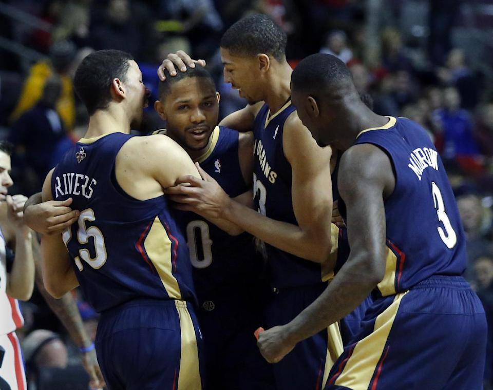 New Orleans Pelicans guard Eric Gordon, second from left, is surrounded by teammates Austin Rivers (25), Anthony Davis and Anthony Morrow (3) after sinking a 2-point shot to defeat the Detroit Pistons 103-101 in an NBA basketball game, Friday, Jan. 24, 2014, in Auburn Hills, Mich. (AP Photo/Duane Burleson)