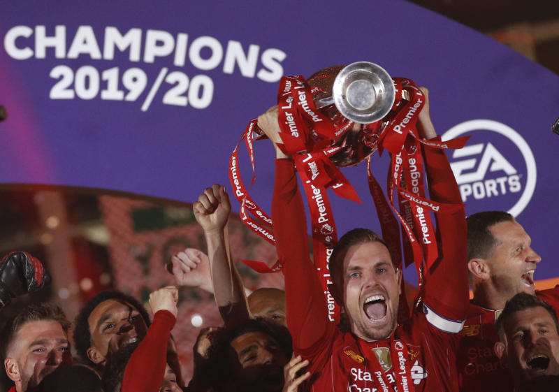 Liverpool's Jordan Henderson, surrounded by his teammates, lifts the English Premier League trophy following the English Premier League soccer match between Liverpool and Chelsea at Anfield Stadium in Liverpool, England, Wednesday, July 22, 2020. Liverpool are champions of the EPL for the season 2019-2020. The trophy is presented at the teams last home game of the season. Liverpool won the match against Chelsea 5-3. (Phil Noble/Pool via AP)