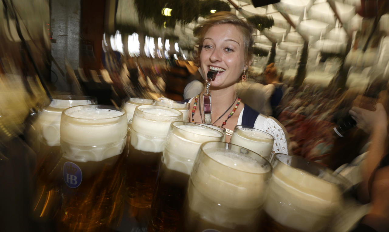 "A waitress carries beer mugs in the Hofbraeuhaus tent after the opening of the famous Bavarian ""Oktoberfest"" beer festival in Munich, southern Germany, Saturday, Sept. 22, 2012. The world's largest beer festival, to be held from Sept. 22 to Oct. 7, 2012 will see some million visitors. (AP Photo/Matthias Schrader) EDS NOTE - SHUTTER SPEED CAUSING BLUR"