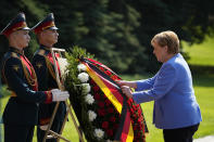 German Chancellor Angela Merkel, right, attends a wreath laying ceremony at the Tomb of Unknown Soldier in Moscow, Russia, Friday, Aug. 20, 2021, prior to talks with Russian President Vladimir Putin. The talks between Merkel and Putin are expected to focus on Afghanistan, the Ukrainian crisis and the situation in Belarus among other issues. (AP Photo/Alexander Zemlianichenko, Pool)