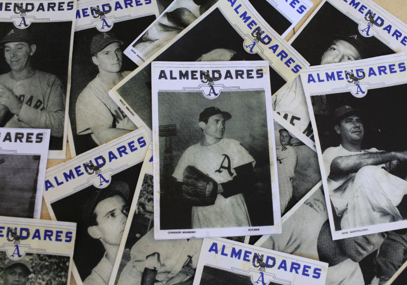"""FILE - This April 25, 2013 file photo shows an old image of Conrado Marrero, center, sitting on top of a collection of photos of his former teammates from the Cuban baseball team Almendares, at his home in Havana, Cuba. Family members say Marrero has died in Havana. He was 102, just two days short of his 103rd birthday. Grandson Rogelio Marrero confirmed the death on Wednesday, April 23, 2014. Marrero was a diminutive right-hander who went by the nickname """"Connie"""" when he pitched for the Washington Senators in the 1950s. (AP Photo/Franklin Reyes, File)"""