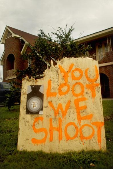 A sign reads 'You Loot We Shoot' in front of a home following Hurricane Isaac in lower Plaquemines Parish on September 2, 2012 in Empire, Louisiana. Today was the first day some residents of lower Plaquemines were allowed to return to assess damage to their homes. (Photo by Mario Tama/Getty Images)