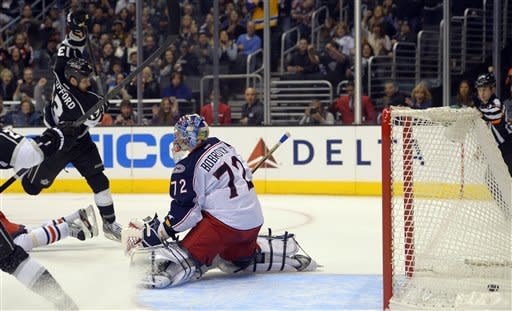 Los Angeles Kings left wing Kyle Clifford, left, scores on Columbus Blue Jackets goalie Sergei Bobrovsky, of Russia, during the second period of their NHL hockey game, Friday, Feb. 15, 2013, in Los Angeles. (AP Photo/Mark J. Terrill)