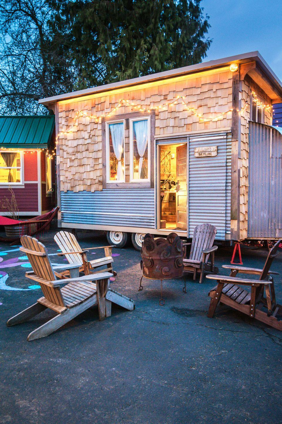 """<p>One of six tiny houses—each built on wheels and outfitted with a bathroom, kitchen, and sleeping loft—at <a href=""""https://tinyhousehotel.com/"""" rel=""""nofollow noopener"""" target=""""_blank"""" data-ylk=""""slk:Caravan Tiny House Hotel"""" class=""""link rapid-noclick-resp"""">Caravan Tiny House Hotel</a> in Portland, Oregon, the <a href=""""https://tinyhousehotel.com/the-tiny-houses/skyline/"""" rel=""""nofollow noopener"""" target=""""_blank"""" data-ylk=""""slk:Skyline"""" class=""""link rapid-noclick-resp"""">Skyline</a> cabin is one of the newest additions to the hotel. The 160-square-foot structure is constructed of mostly salvaged materials and houses two queen beds. Rental rates are $125 per night.</p><p><a class=""""link rapid-noclick-resp"""" href=""""https://go.redirectingat.com?id=74968X1596630&url=https%3A%2F%2Fwww.tripadvisor.com%2FHotel_Review-g52024-d4582522-Reviews-Caravan_The_Tiny_House_Hotel-Portland_Oregon.html&sref=https%3A%2F%2Fwww.oprahdaily.com%2Flife%2Fg35047961%2Ftiny-house%2F"""" rel=""""nofollow noopener"""" target=""""_blank"""" data-ylk=""""slk:PLAN YOUR TRIP"""">PLAN YOUR TRIP</a><br></p>"""