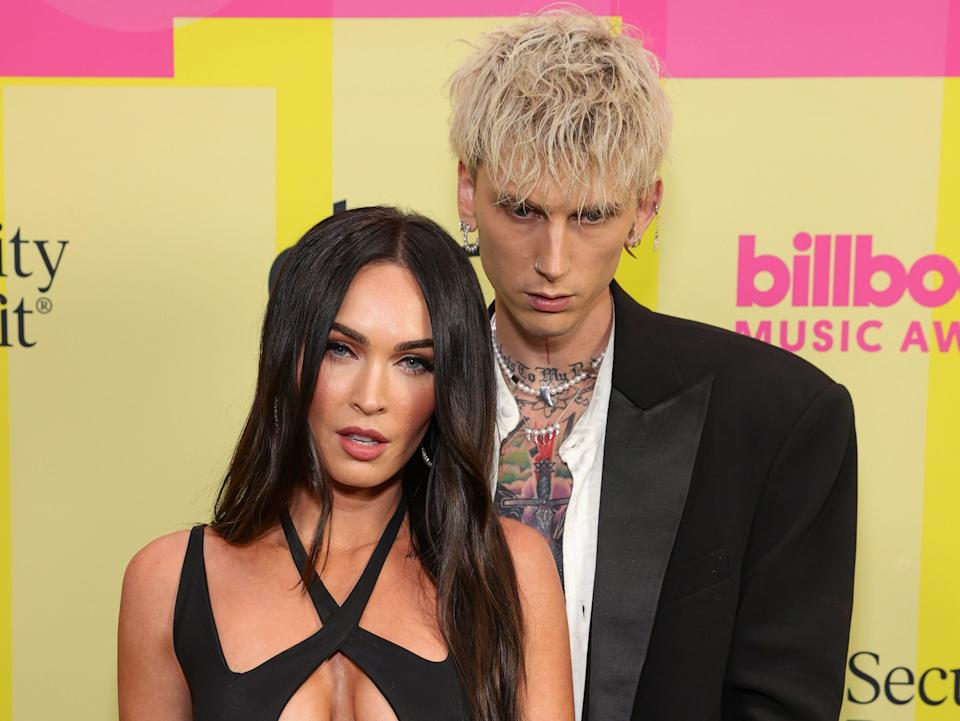 megan fox in a black strappy dress and machine gun kelly in a black suit with an open white button down standing in front of a yellow and pink background