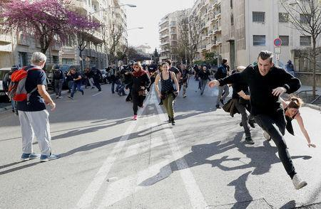 """Protesters run away as tear gas is fired during 19th round of """"yellow vests"""" protests in Nice, France, March 23, 2019. REUTERS/Eric Gaillard"""