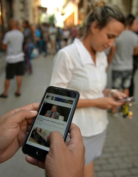 People use their mobile phone to connect to the internet in Havana