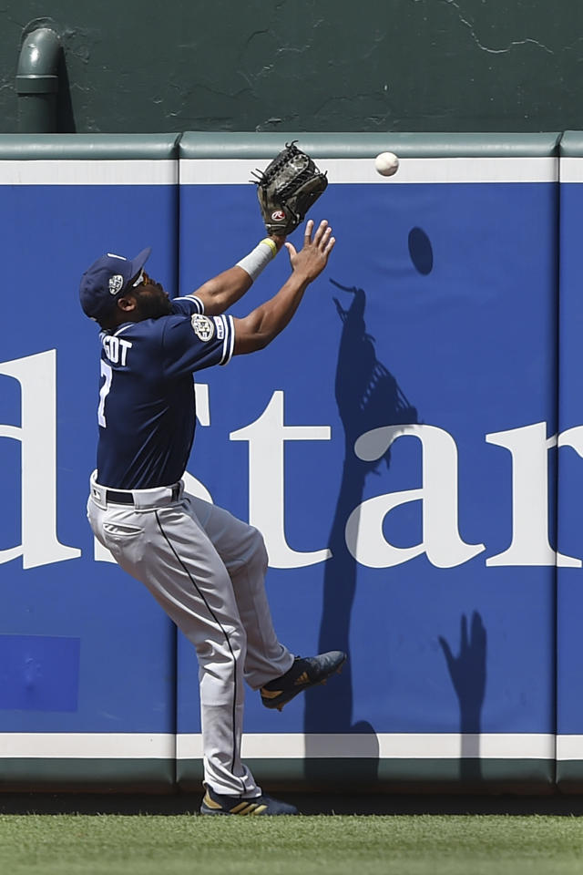 San Diego Padres' Manuel Margot reaches for a ball hit by Baltimore Orioles' Hanser Alberto in the first inning of a baseball game Wednesday, June 26, 2019, in Baltimore. Alberto earned a triple on the play.(AP Photo/Gail Burton)