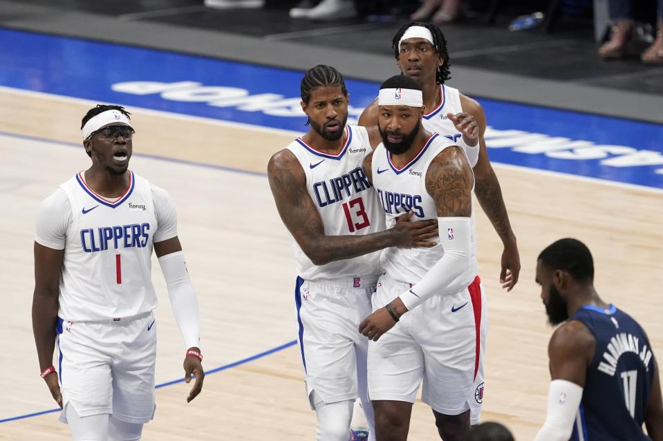 Los Angeles Clippers' Reggie Jackson (1), guard Paul George (13), Marcus Morris Sr., center right, and Terance Mann, rear, celebrate on the way to the bench during a time out as Dallas Mavericks' Tim Hardaway Jr. (11) walks past in the first half in Game 3 of an NBA basketball first-round playoff series in Dallas, Friday, May 28, 2021. (AP Photo/Tony Gutierrez)