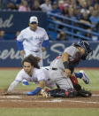 Toronto Blue Jays' Bo Bichette scores on a Cavan Biggio triple, diving past Boston Red Sox catcher Juan Centeno during the fifth inning of a baseball game Thursday, Sept. 12, 2019, in Toronto. (Fred Thornhill/The Canadian Press via AP)