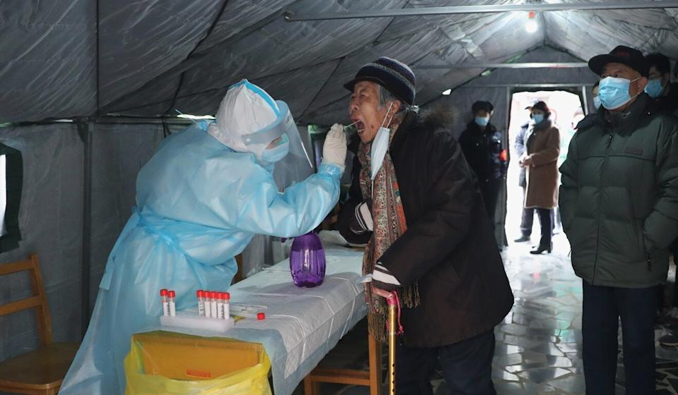 A medical worker collects a swab sample from a resident at a community testing site in Yuhua district in Shijiazhuang. Photo: Xinhua