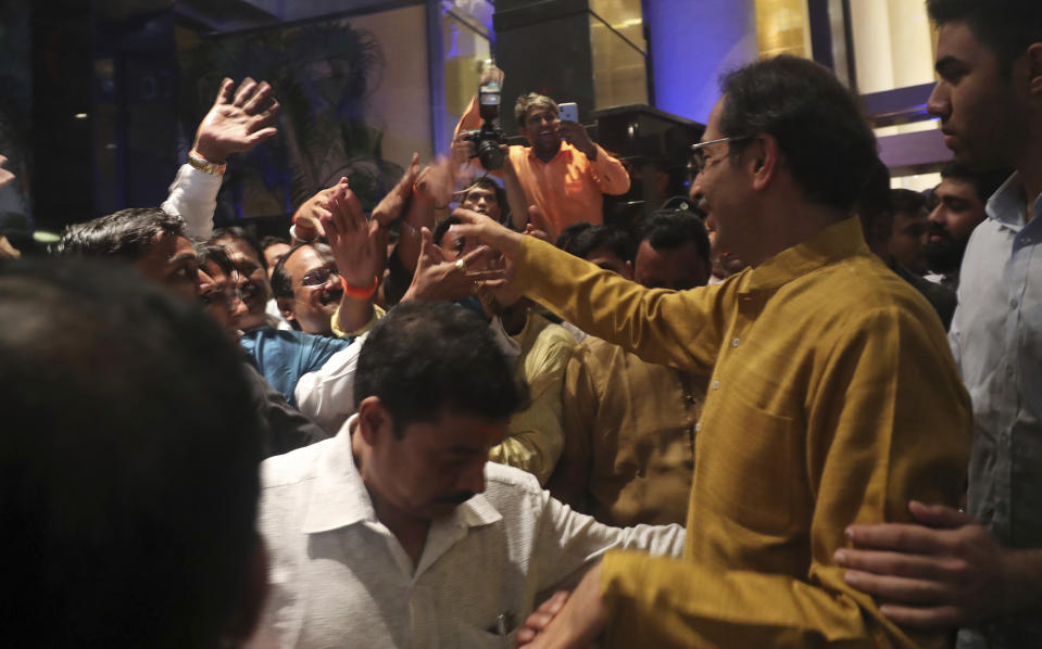 President of the Shiv Sena party Uddhav Thackeray shakes hands with supporters as he leaves after being elected to lead the Shiv Sena, Congress party and Nationalist Congress Party (NCP) alliance in Mumbai, India, Tuesday, Nov. 26, 2019. (AP Photo/Rafiq Maqbool)