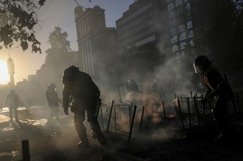 Riot policemen clear the remains of a burnt makeshift barricade during an anti-government protest in Santiago, Chile on Oct. 28, 2019. (Photo: Edgard Garrido/Reuters)