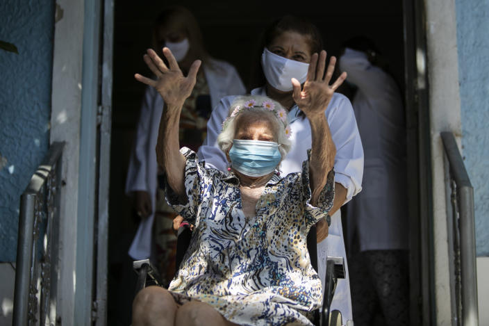 Zelia de Carvalho Morley, 106, waves before receiving a shot of China's Sinovac CoronaVac vaccine for the new coronavirus at the retirement home where she lives in Rio de Janeiro, Brazil, Wednesday, Jan. 20, 2021. De Carvalho Morley lived through the 1918 flu pandemic. (AP Photo/Bruna Prado)