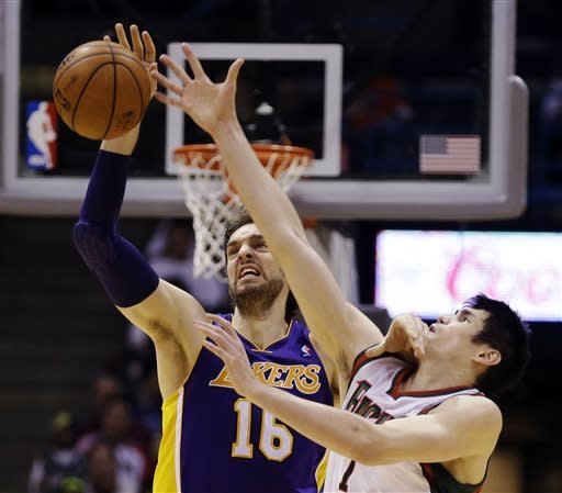 Los Angeles Lakers' Pau Gasol, left, and Milwaukee Bucks' Ersan Ilyasova reach for a loose ball during the second half of an NBA basketball game, Thursday, March 28, 2013, in Milwaukee. The Bucks won 113-103. (AP Photo/Jeffrey Phelps)