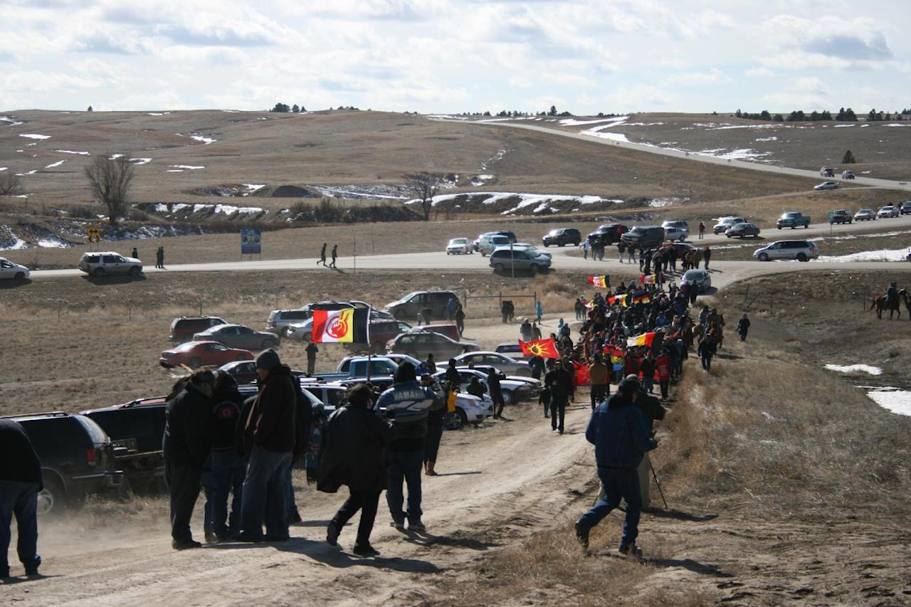 Members of the American Indian Movement walk to the Wounded Knee Massacre Monument Wednesday, Feb. 27, 2013 in Wounded Knee, S.D. Wednesday marked the 40th anniversary of the start of the 71-day occupation in the village of Wounded Knee on the Pine Ridge Indian Reservation. Hundreds of AIM members and other supporters turned out for a day of ceremonies to commemorate the anniversary of the fatal standoff that drew national attention to the impoverished reservation and the plight of local tribes.. (AP Photo/Kristi Eaton)