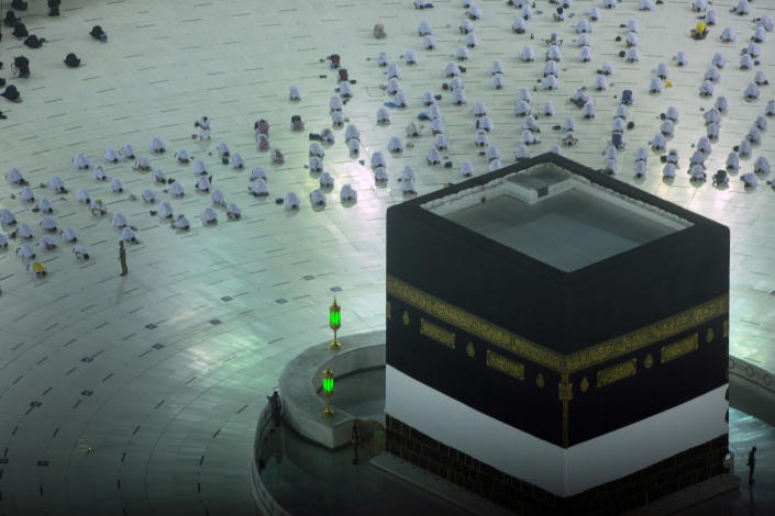 Muslim pilgrims pray in front of the Kaaba, the cubic building at the Grand Mosque, as they keep social distancing, at the start the annual hajj pilgrimage, Sunday, July 18, 2021. The pilgrimage to Mecca required once in a lifetime of every Muslim who can afford it and is physically able to make it, used to draw more than 2 million people. But for a second straight year it has been curtailed due to the coronavirus with only vaccinated people in Saudi Arabia able to participate. (AP Photo/Amr Nabil)