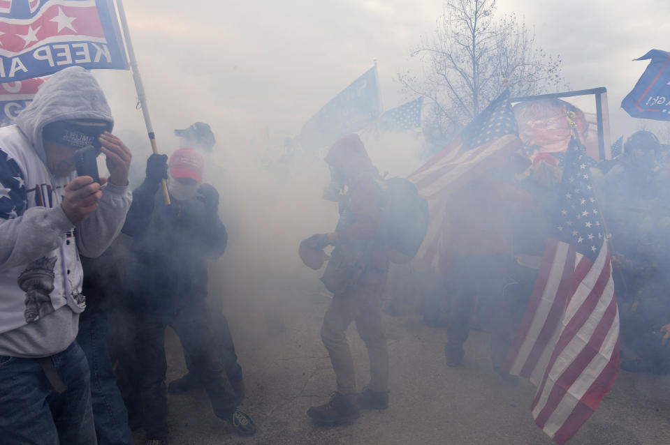 Trump supporters clash with police and security forces as they try to storm the US Capitol surrounded by tear gas in Washington, DC on January 6, 2021. (Photo by JOSEPH PREZIOSO/AFP via Getty Images)