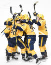 Nashville Predators left wing Daniel Carr is mobbed by teammates after scoring the winning goal against the St. Louis Blues during a shootout in an NHL hockey game Monday, Nov. 25, 2019, in Nashville, Tenn. The Predators won 3-2. (AP Photo/Mark Zaleski)