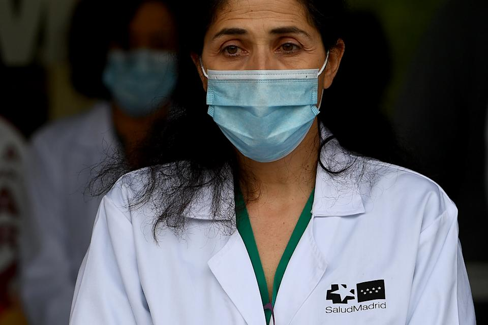 Healthcare workers observe a minute of silence to pay tribute to their fallen colleagues outside the Gregorio Maranon Hospital in Madrid on May 14, 2020, during the national lockdown to prevent the spread of the COVID-19 disease. (Photo by Gabriel BOUYS / AFP) (Photo by GABRIEL BOUYS/AFP via Getty Images)
