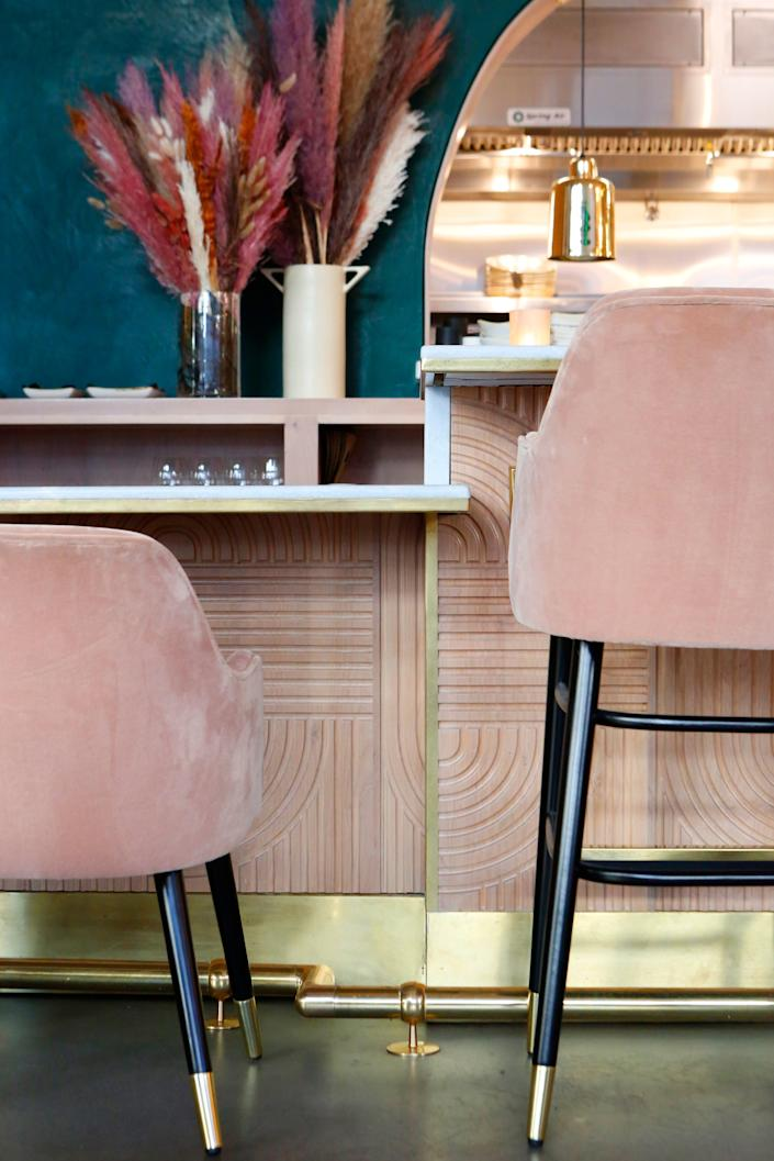 """<div class=""""caption""""> The geometric pattern on the bar face was chiseled into wood panels and stained a light blush. The end result almost looks like a plush fabric, mimicking the bar stools. </div> <cite class=""""credit"""">Lu Tapp</cite>"""
