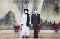FILE - In this July 28, 2021, file photo released by China's Xinhua News Agency, Taliban co-founder Mullah Abdul Ghani Baradar, left, and Chinese Foreign Minister Wang Yi pose for a photo during their meeting in Tianjin, China. In the U.S. departure from Afghanistan, China has seen the realization of long-held hopes for a reduction of the influence of a geopolitical rival in what it considers its backyard. Yet, it is also deeply concerned that the very withdrawal could bring instability to that backyard - Central Asia - and possibly even spill over the border into China itself in its heavily Muslim northwestern region of Xinjiang. (Li Ran/Xinhua via AP, File)
