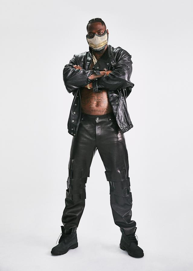 """<cite class=""""credit"""">Jacket, $5,400, by Gucci / Pants, $5,700, by Bottega Veneta / Boots, $198, by Timberland / Jewelry and mask, his own</cite>"""