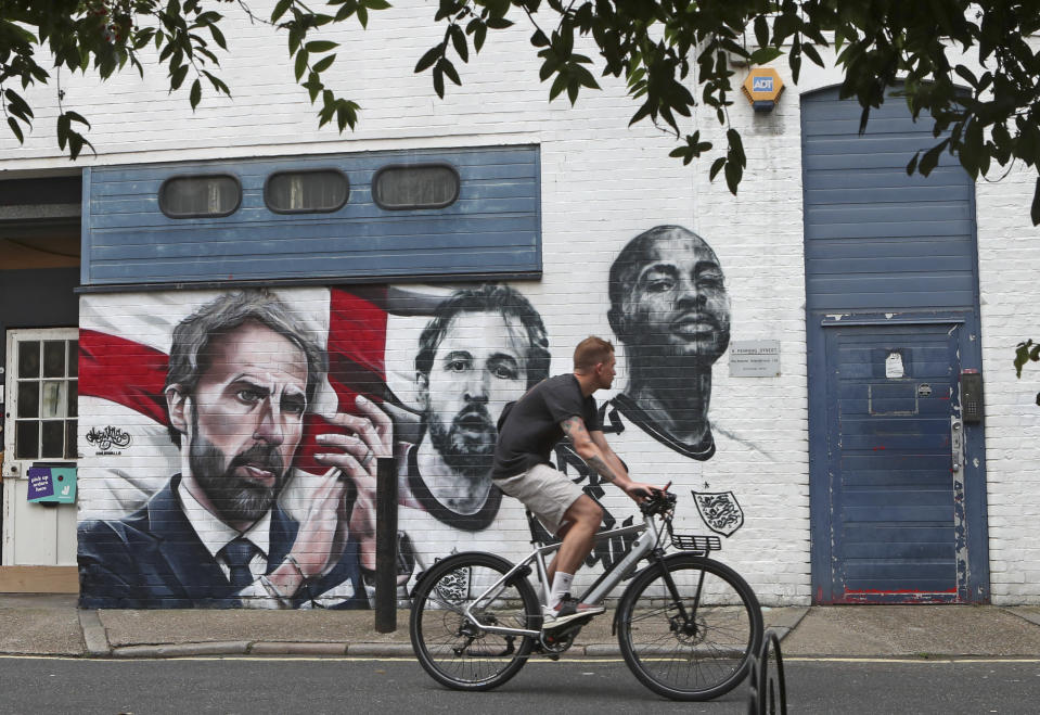 A man cycles past a mural depicting England's manager Gareth Southgate, captain Harry Kane and Raheem Sterling, from left, painted on a wall near Vinegar Yard in south London, Wednesday July 14, 2021. England lost the Euro 2020 soccer championship final match to Italy on Sunday July 11. (AP Photo/Tony Hicks)