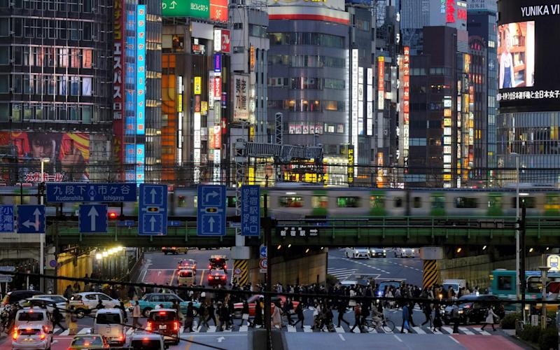 People cross a street near Tokyo's entertainment district Kabukicho (background) on March 31, 2020. - Tokyo Governor Yuriko Koike on March 30 urged residents to stay away from karaoke parlours, bars and nightclubs to prevent the COVID-19 coronavirus from spreading - Kazuhiro Nogi/AFP