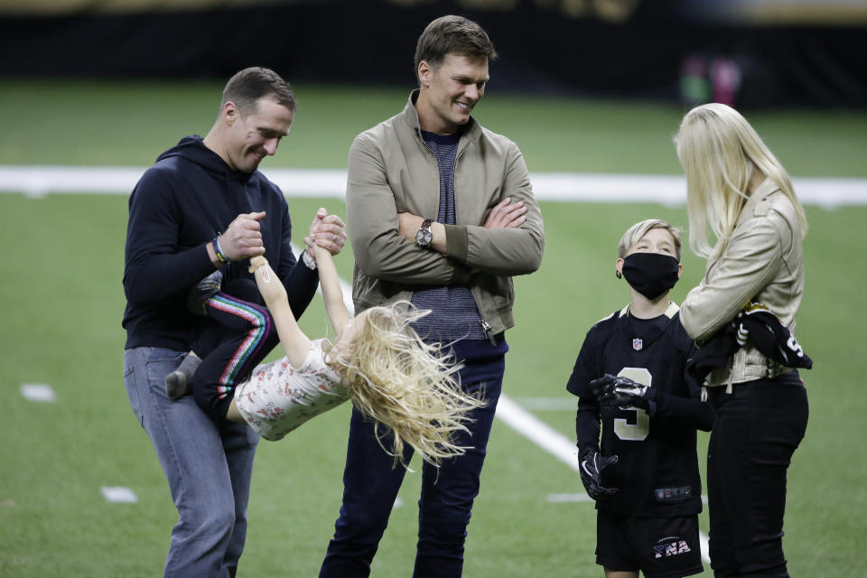 New Orleans Saints quarterback Drew Brees, left, plays with his children as Tampa Bay Buccaneers quarterback Tom Brady speaks with Brittany Brees after the Saints' loss. (AP Photo/Butch Dill)