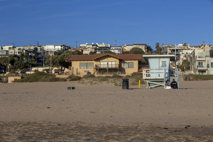 A couple sit on the lifeguard tower between 26th and 27th Streets at Bruce's Beach, which is part of the Bruce property.