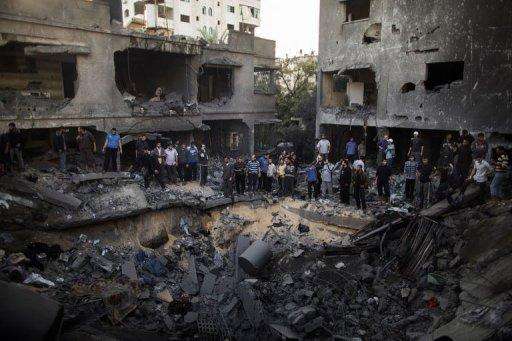 Palestinian men gather around a crater caused by an Israeli air strike on the Dallu family's home in Gaza City. Six members of the family were killed when an Israeli missile struck their neighbourhood
