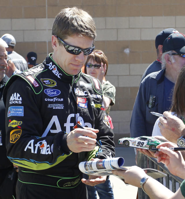 Driver Carl Edwards signs autographs Friday, May 9, 2014, at Kansas Speedway in Kansas City, Kan., for Saturday night's NASCAR Sprint Cup series auto race. (AP Photo/Colin E. Braley)
