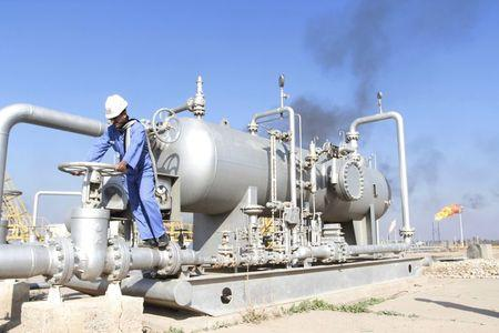 A worker checks the valve of an oil pipe at Nahr Bin Umar oil field, north of Basra, Iraq