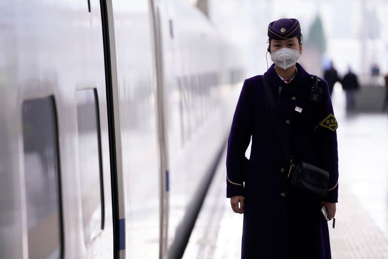 A train staff wearing a mask is seen at the Shanghai railway station in Shanghai