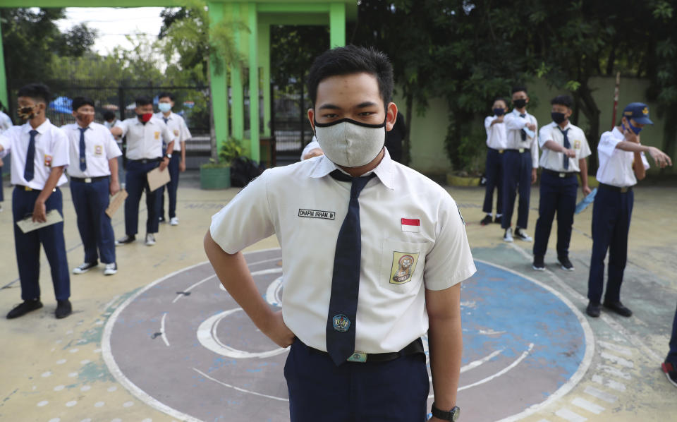 Students wearing face masks as a precaution against the new coronavirus line up at their school during the first day of reopening of state high schools in Bekasi on the outskirts of Jakarta, Indonesia, July 13, 2020. (AP Photo/Achmad Ibrahim)