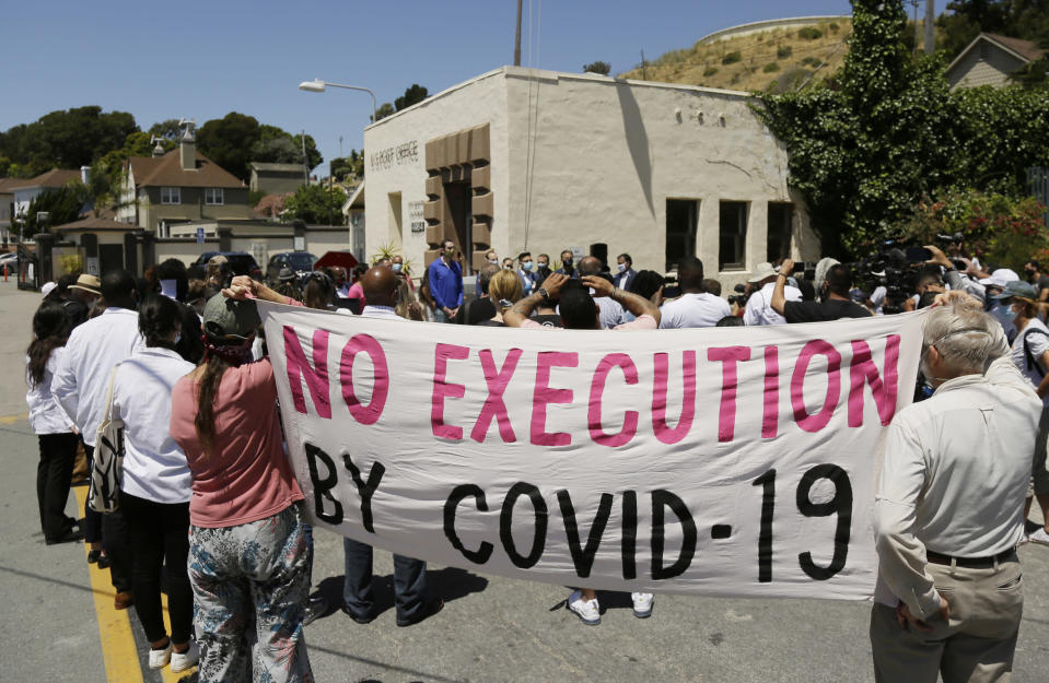 "FILE - In this July 9, 2020, file photo, people hold up a banner while listening to a news conference outside San Quentin State Prison in San Quentin, Calif. The group of legislators, advocates, academics and public health officials gathered outside San Quentin State Prison to discuss a COVID-19 outbreak at the facility that has sickened more than 1,400 inmates with six deaths. A California appeals court has ordered state corrections officials to cut the population of one of the world's most famous prisons to less than half of its designed capacity, citing officials' ""deliberate indifference"" to the plight of inmates during the coronavirus pandemic. State prison officials said Wednesday, Oct. 21, 2020, that they are deciding whether to appeal the order, which otherwise will force them to parole or transfer about 1,100 inmates serving time in San Quentin State Prison north of San Francisco. (AP Photo/Eric Risberg, File)"