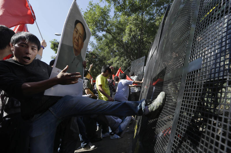 Chinese protesters kick the barricades during an anti-Japan protest outside the Japanese embassy in Beijing, Saturday, Sept. 15, 2012. Tensions between the two countries flared anew after the Japanese government bought the disputed islands from their private Japanese owners this week. The uninhabited islands, Senkaku in Japan and Diaoyu in China, claimed by both countries as well as Taiwan, have become a rallying point for nationalists on both sides. (AP Photo/Ng Han Guan)