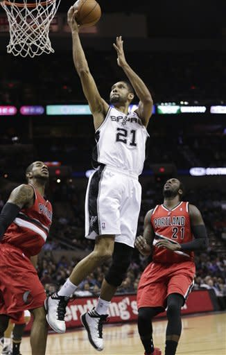 San Antonio Spurs' Tim Duncan (21) shoots over Portland Trail Blazers' LaMarcus Aldridge, left, and J.J. Hickson, right, during the first half of an NBA basketball game on Friday, March 8, 2013, in San Antonio. (AP Photo/Eric Gay)