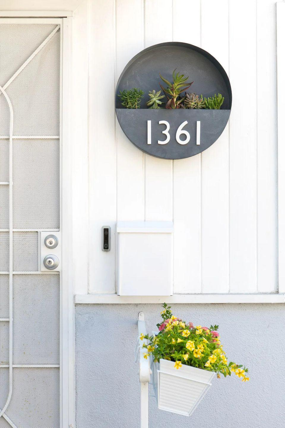 """<p>Swap out your out-of-date house numbers for a gorgeous wall planter display featuring assorted succulents. </p><p><strong>Get the tutorial at <a href=""""https://sarahhearts.com/diy-house-number-planter-rental-friendly-front-porch-decor/"""" rel=""""nofollow noopener"""" target=""""_blank"""" data-ylk=""""slk:Sarah Hearts"""" class=""""link rapid-noclick-resp"""">Sarah Hearts</a>.</strong></p><p><a class=""""link rapid-noclick-resp"""" href=""""https://go.redirectingat.com?id=74968X1596630&url=https%3A%2F%2Fwww.walmart.com%2Fip%2FEclectic-E6000-Industrial-Adhesive-3-fl-oz-Clear-or-Transparent%2F44148643&sref=https%3A%2F%2Fwww.thepioneerwoman.com%2Fhome-lifestyle%2Fgardening%2Fg36556911%2Fdiy-planters%2F"""" rel=""""nofollow noopener"""" target=""""_blank"""" data-ylk=""""slk:SHOP GLUE"""">SHOP GLUE</a></p>"""