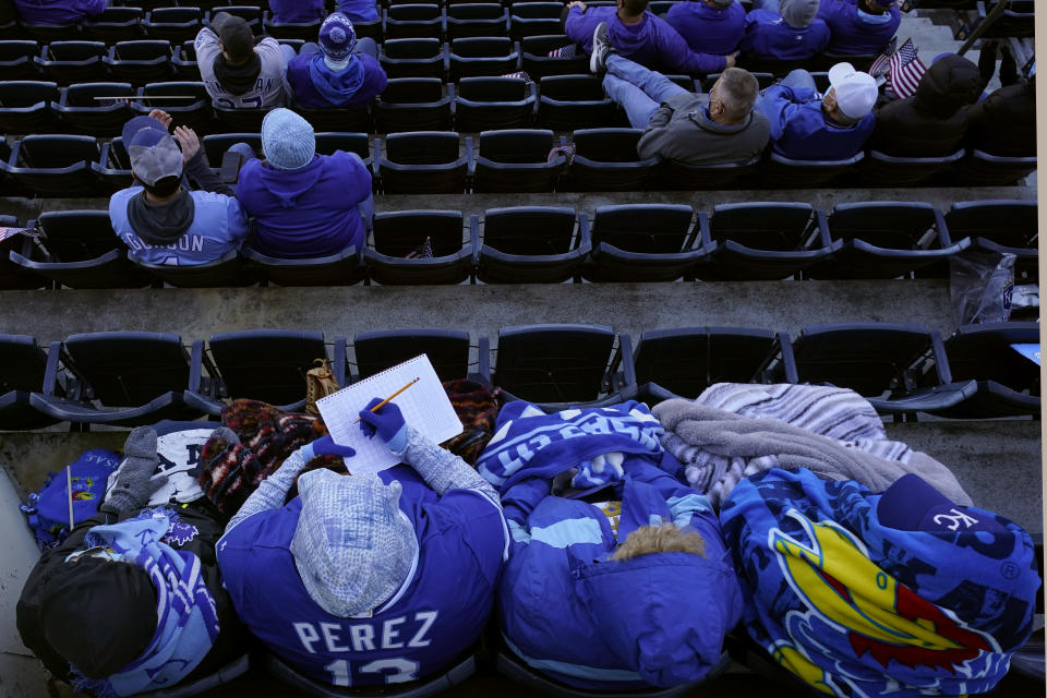 A fan keeps score during the first inning of a baseball game between the Kansas City Royals and the Texas Rangers, Thursday, April 1, 2021, in Kansas City, Mo. (AP Photo/Charlie Riedel)