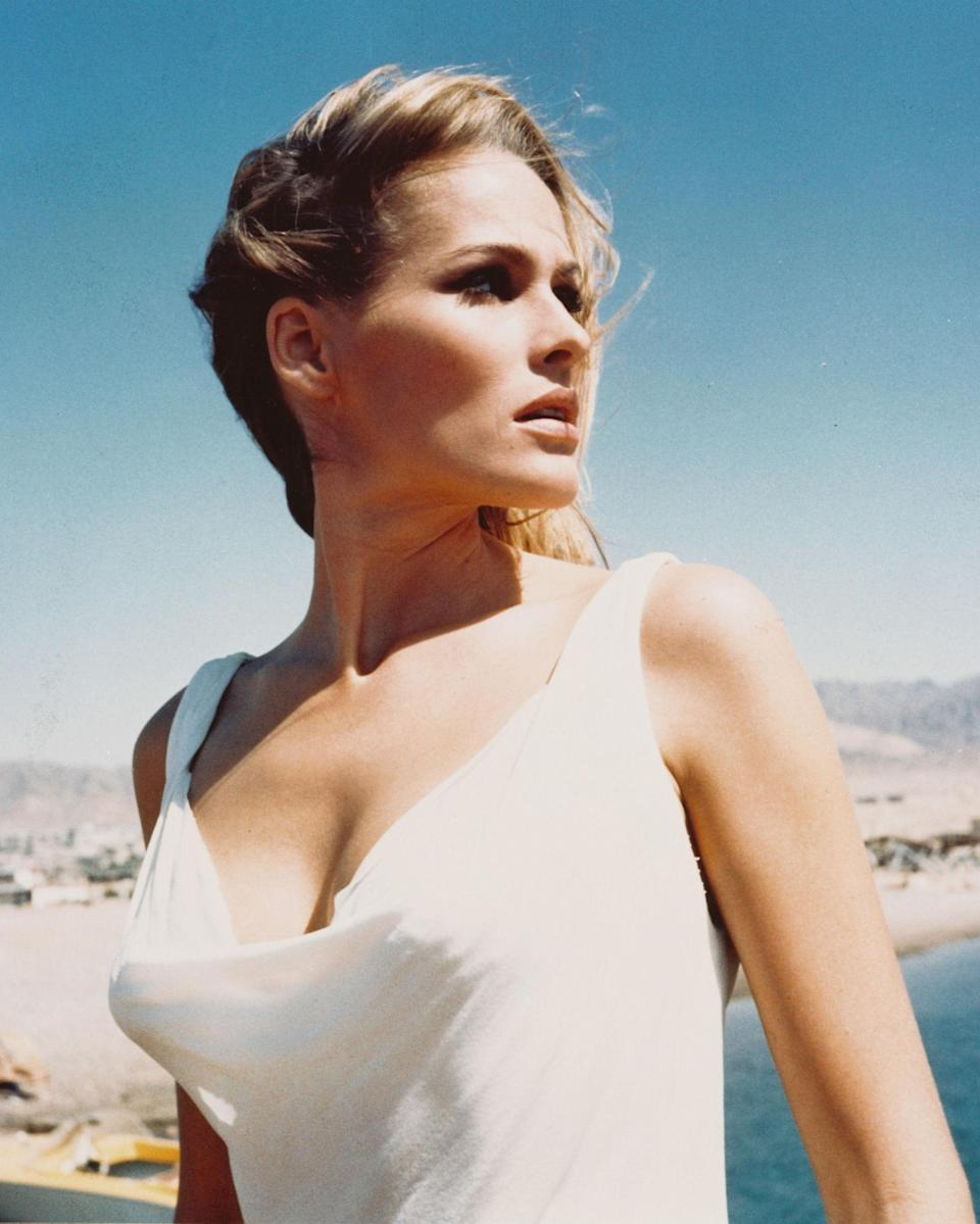 """<p>Best known as the original Bond girl having starred alongside Sean Connery in <em>Dr. No</em>, Ursula Andress' <a href=""""https://www.youtube.com/watch?v=AZ6mOC4uSX4&t=42s"""" rel=""""nofollow noopener"""" target=""""_blank"""" data-ylk=""""slk:entrance in that film"""" class=""""link rapid-noclick-resp"""">entrance in that film</a> as (cringe) 'Honey Ryder the shell diver' was voted #1 'greatest sexy movie moment' in a Channel 4 survey some forty years later. """"This bikini made me into a success. As a result of starring in <i>Dr. No</i> as the first Bond girl, I was given the freedom to take my pick of future roles and to become financially independent,"""" she later said of the white two-piece still etched into the minds of generations of movie-goers.</p>"""