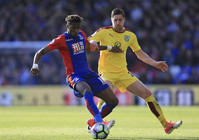 <p>Crystal Palace's Wilfried Zaha, left, and Burnley's Stephen Ward battle for the ball </p>