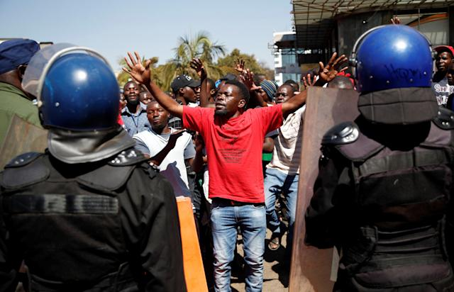<p>A supporter of the Movement for Democratic Change (MDC) opposition party of Nelson Chamisa gestures to the riot police as they march on the streets of Harare, Zimbabwe, August 1, 2018. (Photo: Siphiwe Sibeko/Reuters) </p>