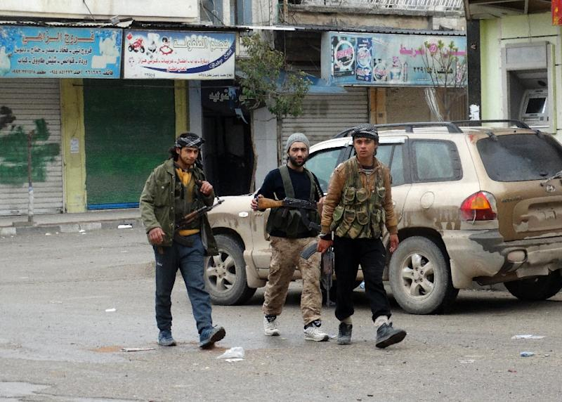 Fighters loyal to Al-Qaeda's Syrian affiliate and its allies walk through the northwestern Syrian city of Idlib on March 28, 2015