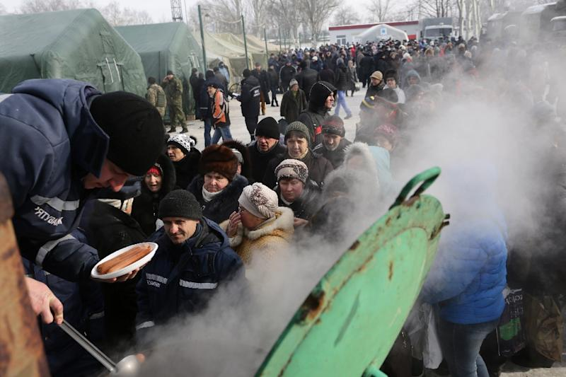 Rescue workers give food to residents in the Ukrainian town of Avdiivka on February 1, 2017 amid a spike in clashes between government forces and Russian-backed separatists (AFP Photo/Aleksey FILIPPOV)